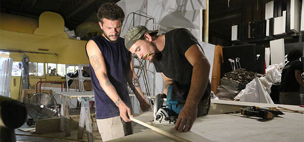 two men making wooden prop