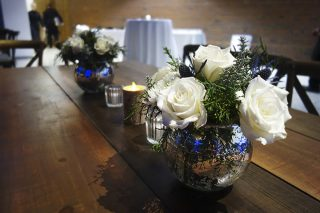 White roses in vase on wood table