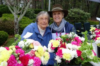 two ladies behind bouquets