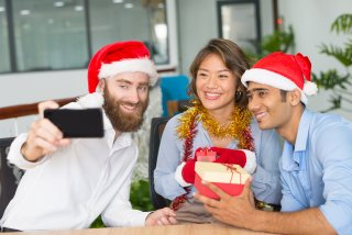 Cheerful business team taking Christmas selfie